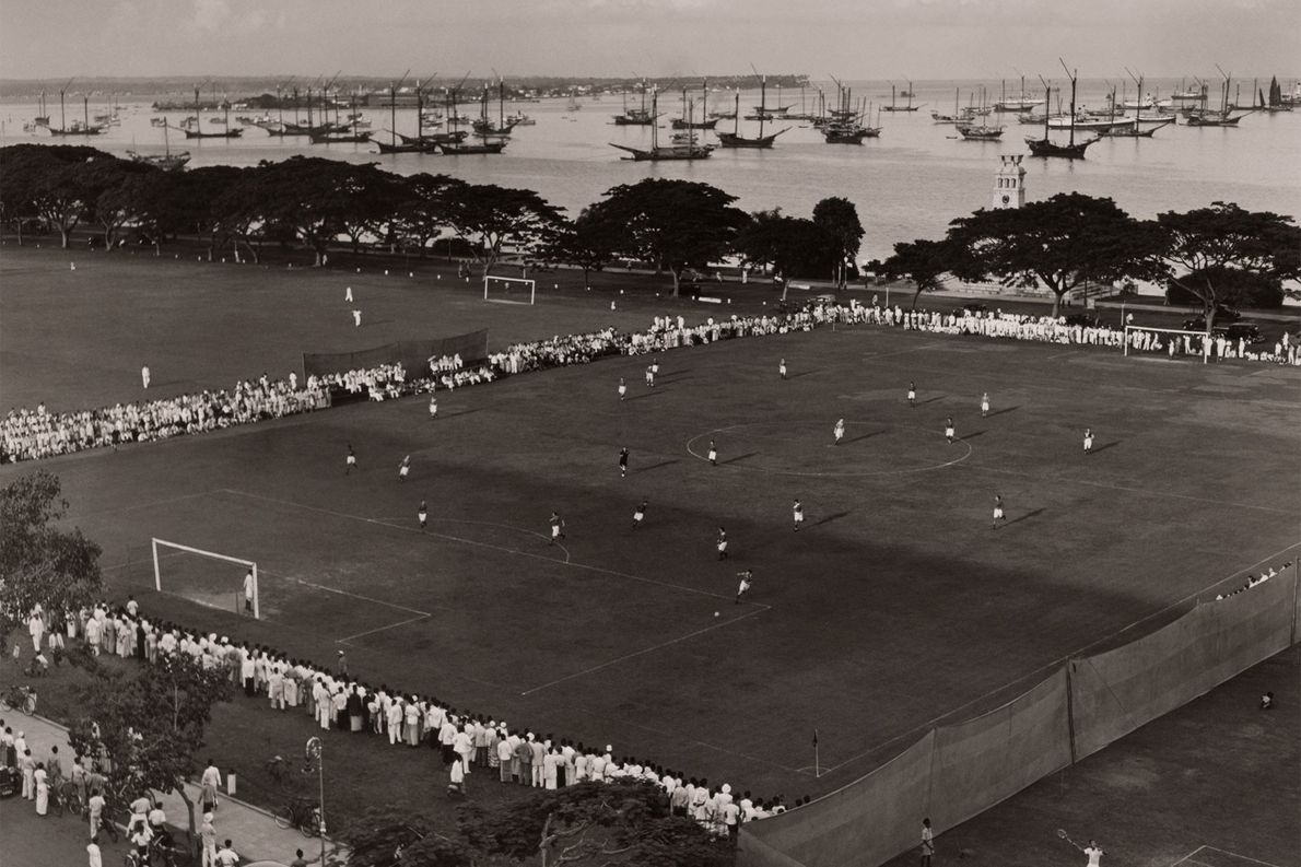 Spectators surround a portside soccer field in the Pacific Islands. Early Europeans brought the sport to ...