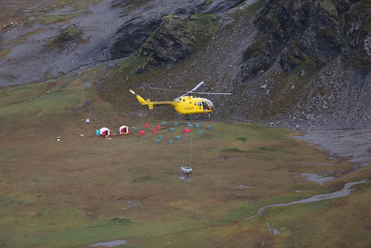 """A helicopter moves a bait bucket, in view of """"Team Rat's"""" camp, where workers stayed."""