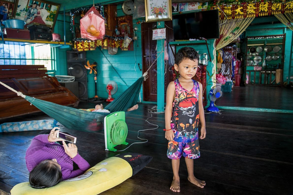Chan, pictured on the right, plays at home while his mother, on the left, looks at …