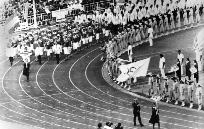 Dick Palmer, secretary of Britain's Olympic team, right foreground, carries the Olympic banner to represent the ...