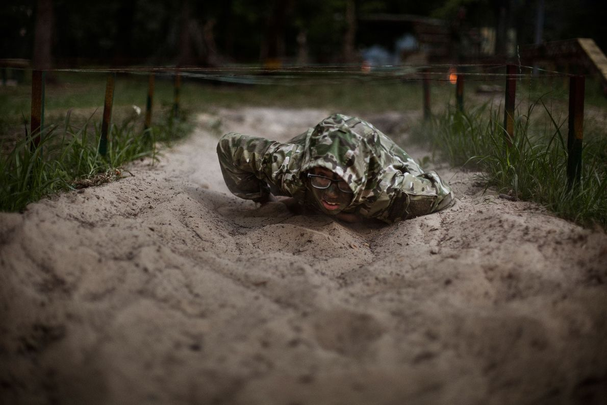 "Mathew, 11, crawls under barbed wire during military exercises at LIDER camp. ""I decided to join ..."