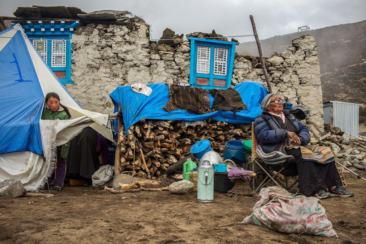 Pem Phurti Sherpa rests in front of her damaged home as her granddaughter peers through their ...