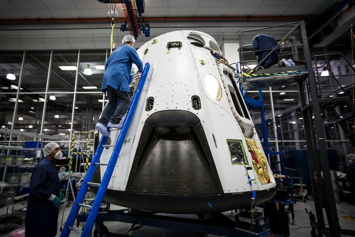 SpaceX engineers work on the Crew Dragon capsule ahead of its milestone flight.