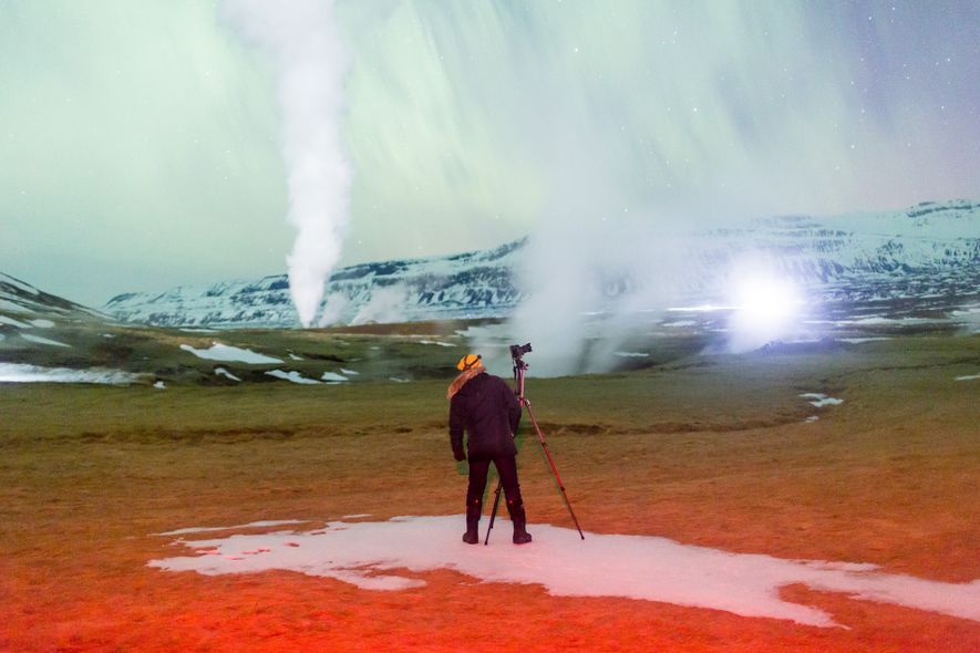 Steam from geothermal activity softens the aurora-filled sky over Iceland.