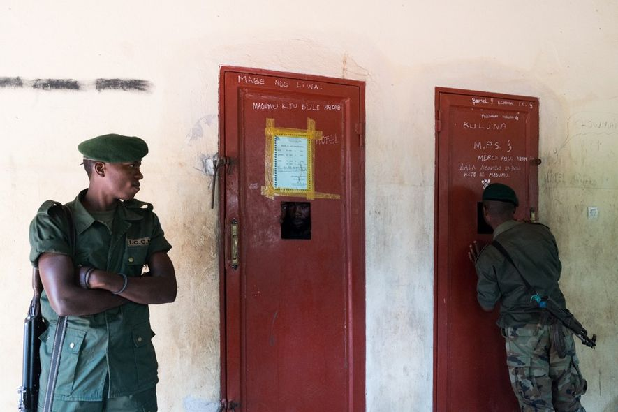 Guards in the town of Epulu watch over two men who were arrested after being caught with eight diamonds while mining inside the Okapi Wildlife Reserve.