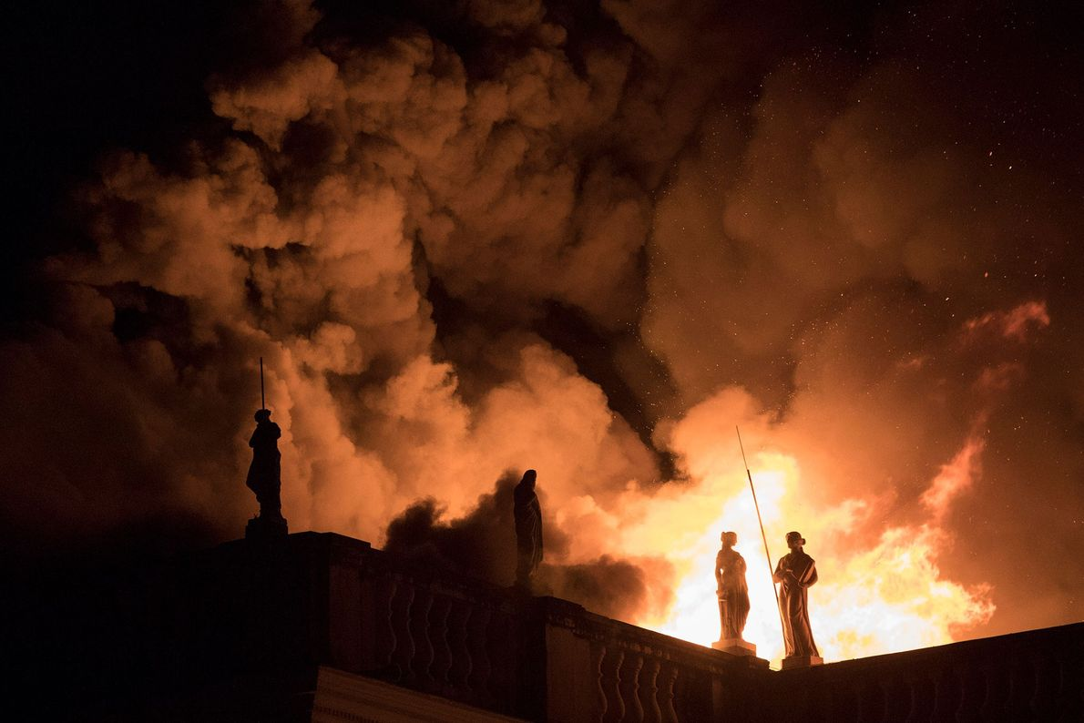 Flames erupt from the museum's roof, backlighting the statues fringing its upper levels. The museum is ...