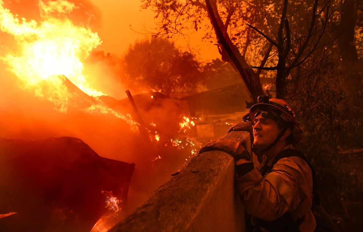 Mayor of Malibu and firefighter Rick Mullen surveys a burning house caught in the Woolsey Fire.
