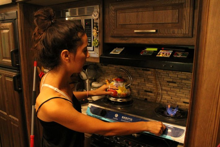 Enas lights the biogas stove she uses in the off-grid RV home she shares with Culhane. ...