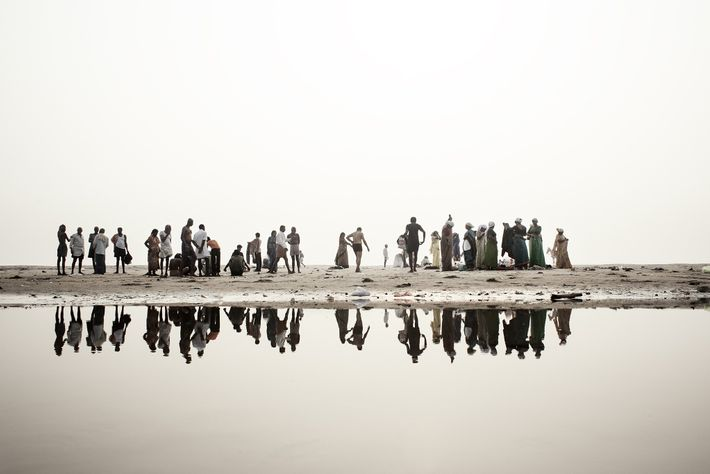 Hindu devotees along the banks of the Ganges get ready to bathe in the water of ...