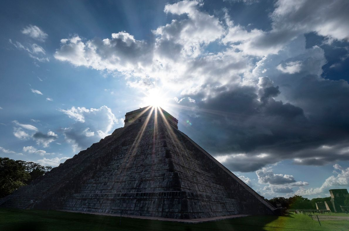 The El Castillo pyramid in Chichen Itza, Mexico, is backlit by the setting sun. For a ...