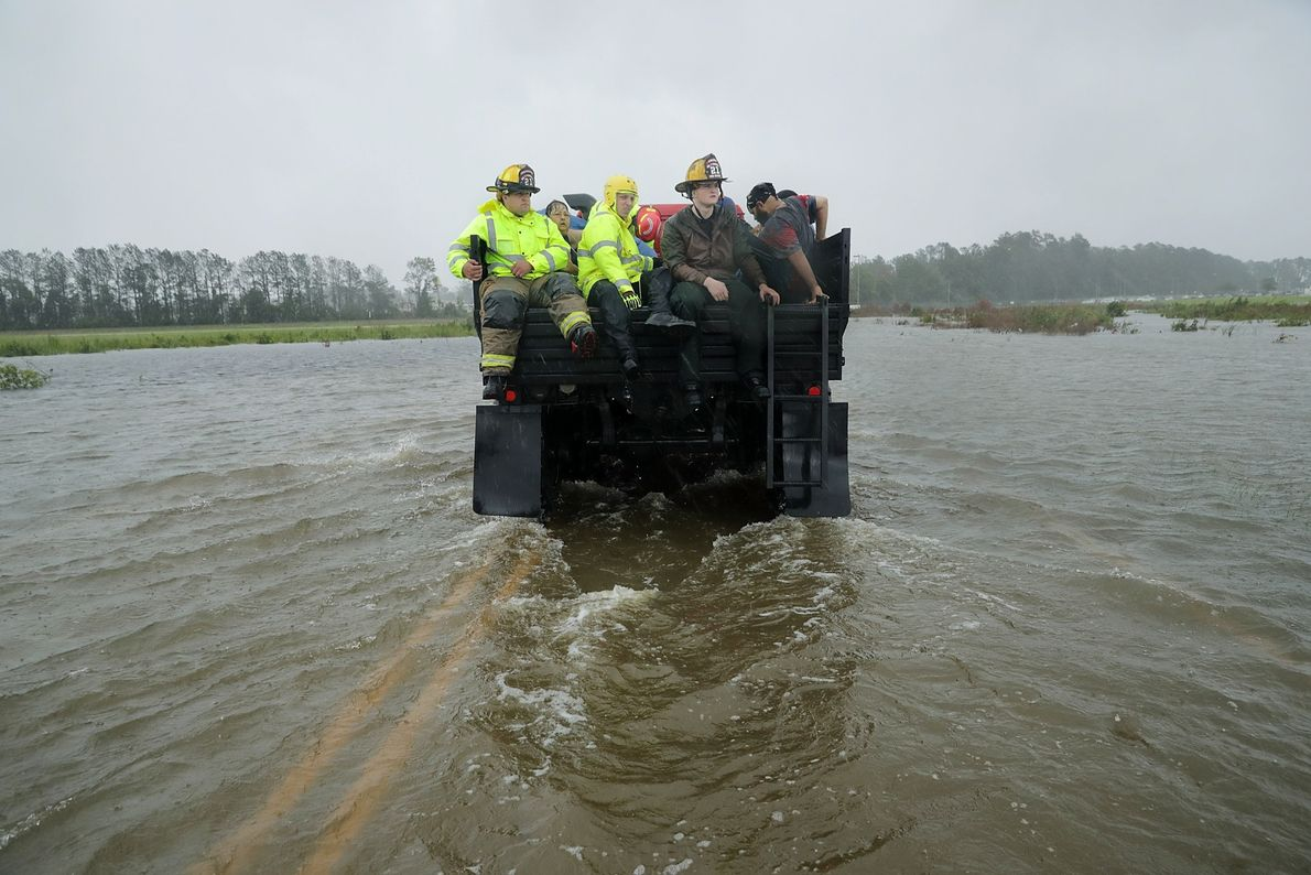 Fire department rescue workers and volunteers from the Civilian Crisis Response Team use a truck to ...