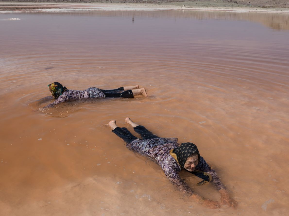 Women play in the red waters of what remains of Lake Urmia.