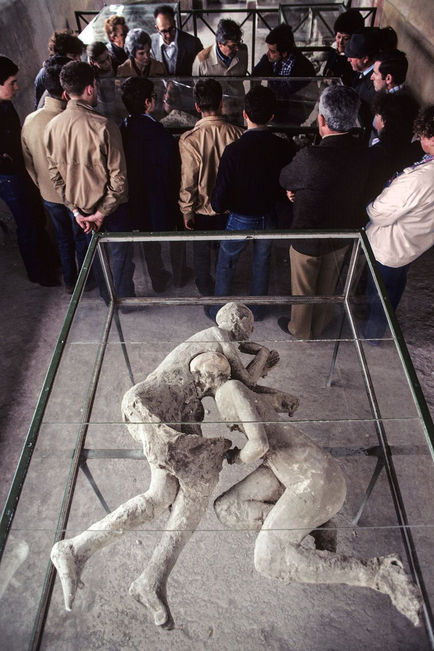 A group studies body casts in the House of Cryptoporticus while touring the ruins of Pompeii. ...
