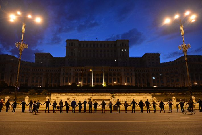 People stand together to form a human chain around the Romanian Parliament building in Bucharest on ...