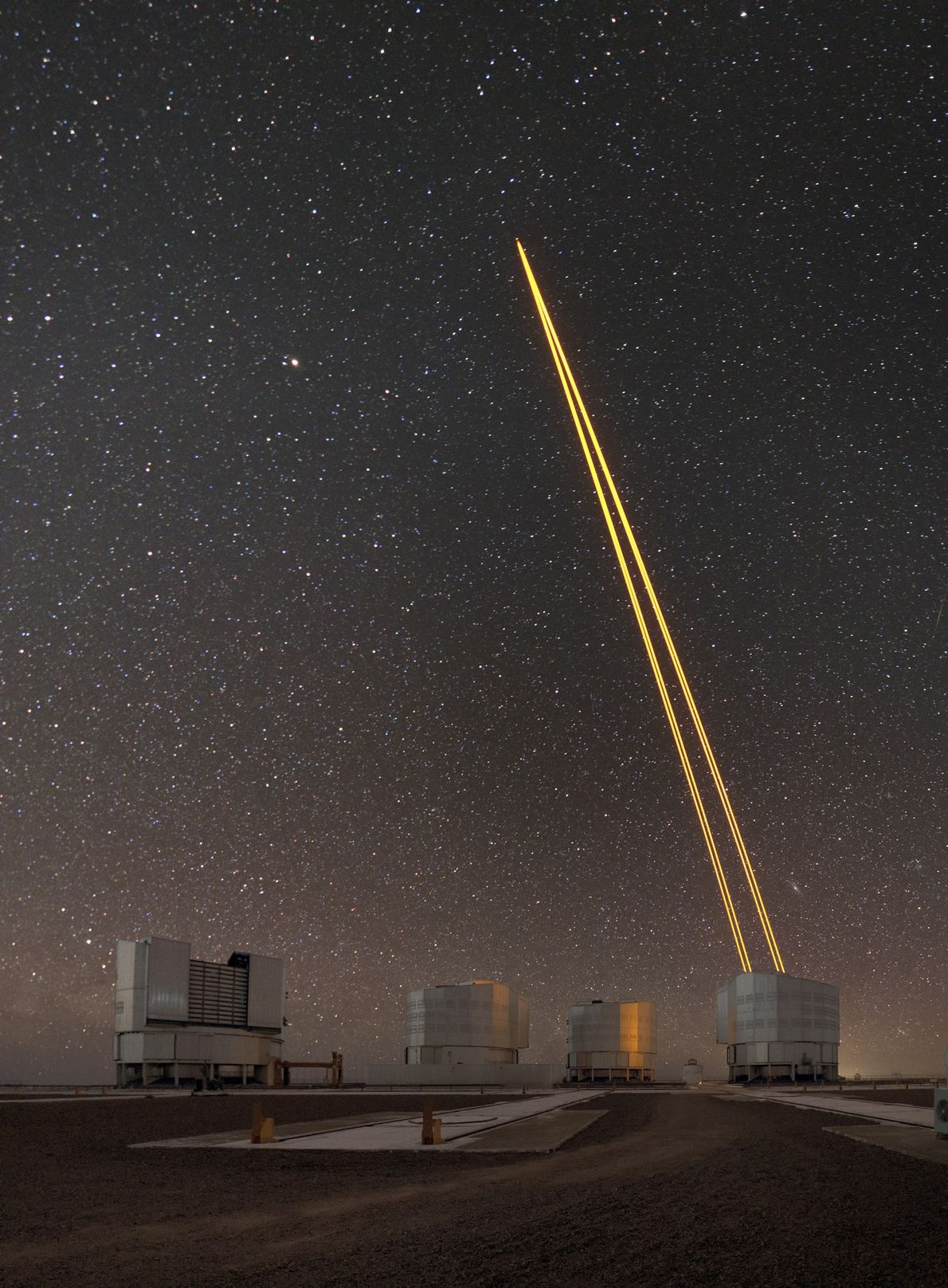 Laser light creates an artificial guide star for the European Southern Observatory's Very Large Telescope in ...