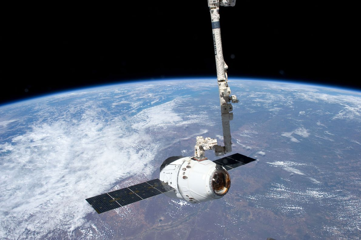 With Earth looming behind it as an epic backdrop, a SpaceX Dragon craft docked with the ...