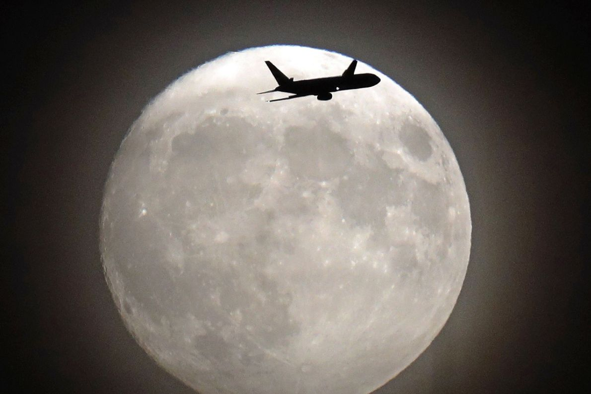 A commerical jet flies in front of the November 2016 supermoon on its approach to Heathrow ...