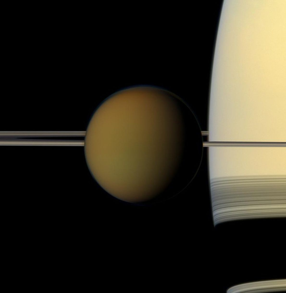 The colourful globe of Saturn's largest moon, Titan, passes in front of the planet and its ...