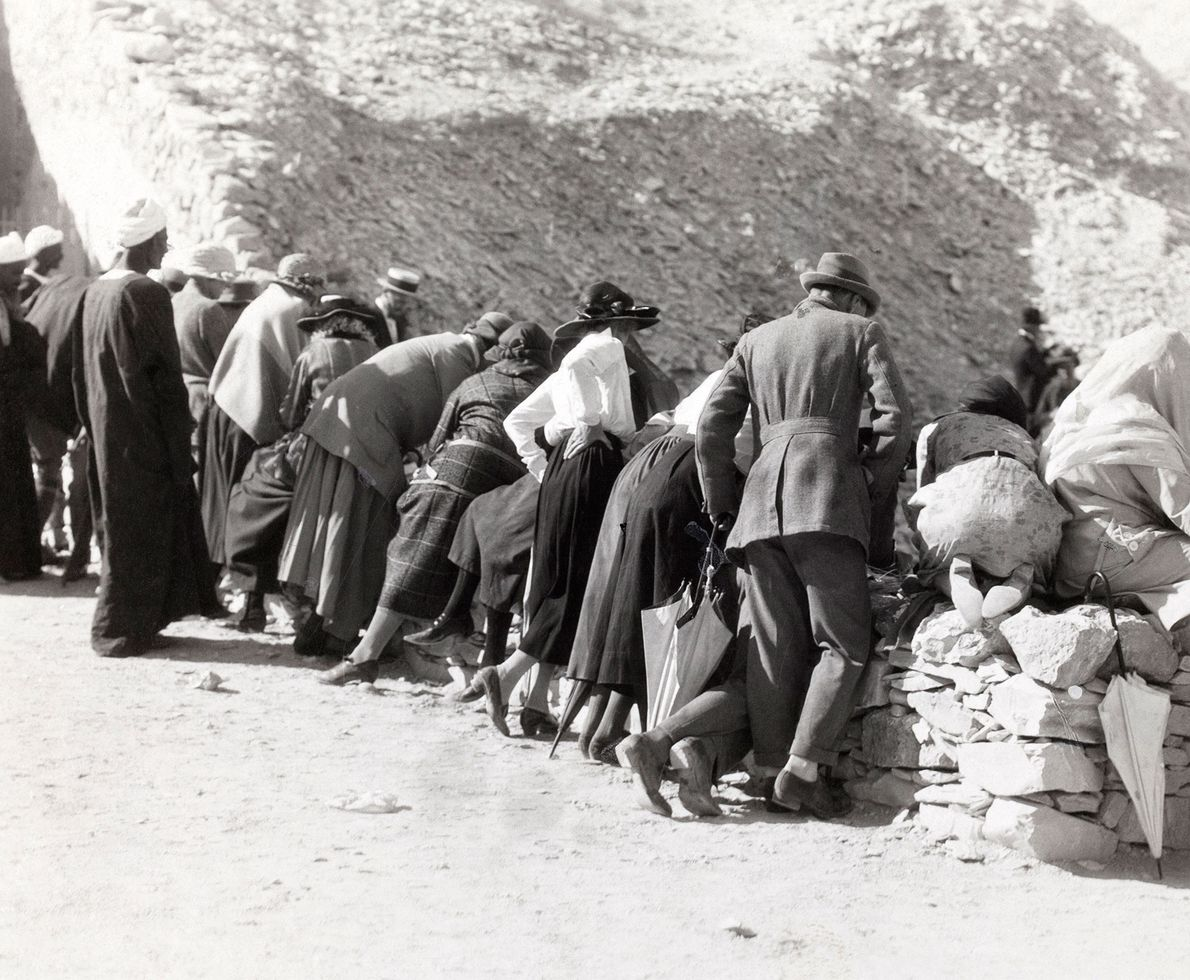 Crowding along the retaining wall above King Tut's tomb, spectators lean in to hear the press ...