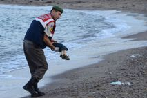 A Turkish police officer gently carries the body of three-year-old Aylan Kurdi after he washed ashore. ...