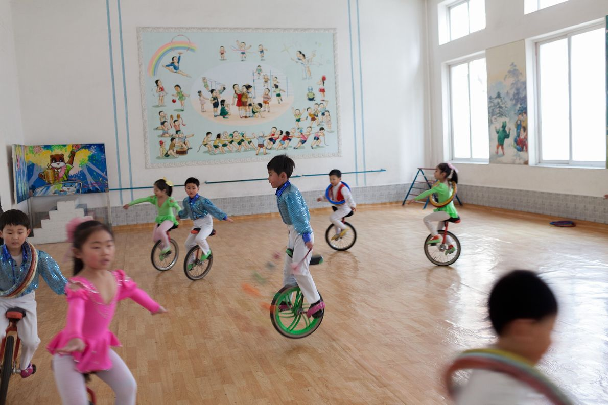 Kindergarteners practise riding unicycles in a Pyongyang gymnasium.