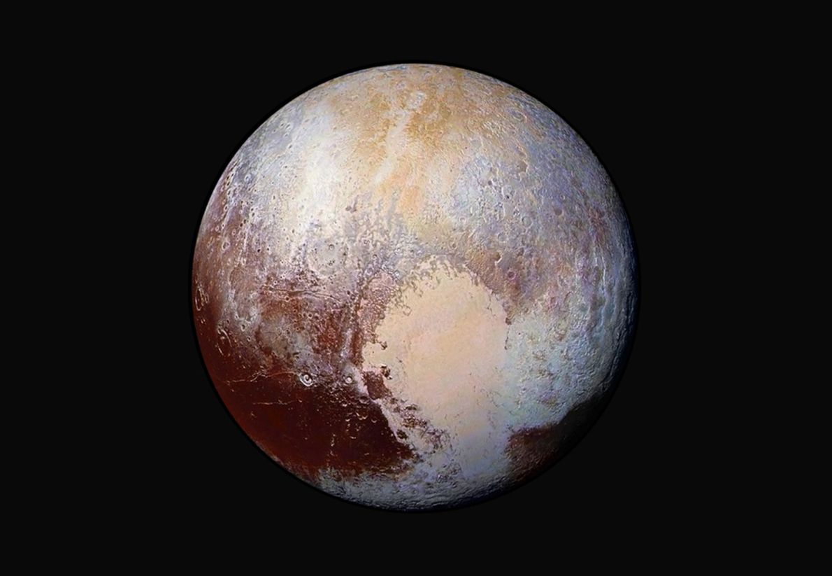 This enhanced colour image reveals Pluto's remarkably blotchy surface, punctuated by regions that are very dark ...