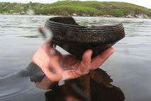 A diver holds a Neolithic (ca. 3,500 B.C) Ustan vessel found near a crannog (artificial island) ...