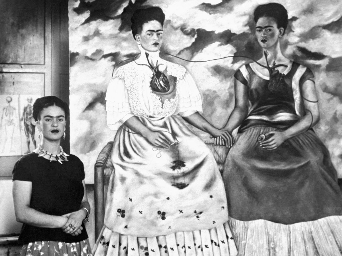 Artist Frida Kahlo stands by her painting, entitled Me Twice, on October 24, 1939. Kahlo, like ...