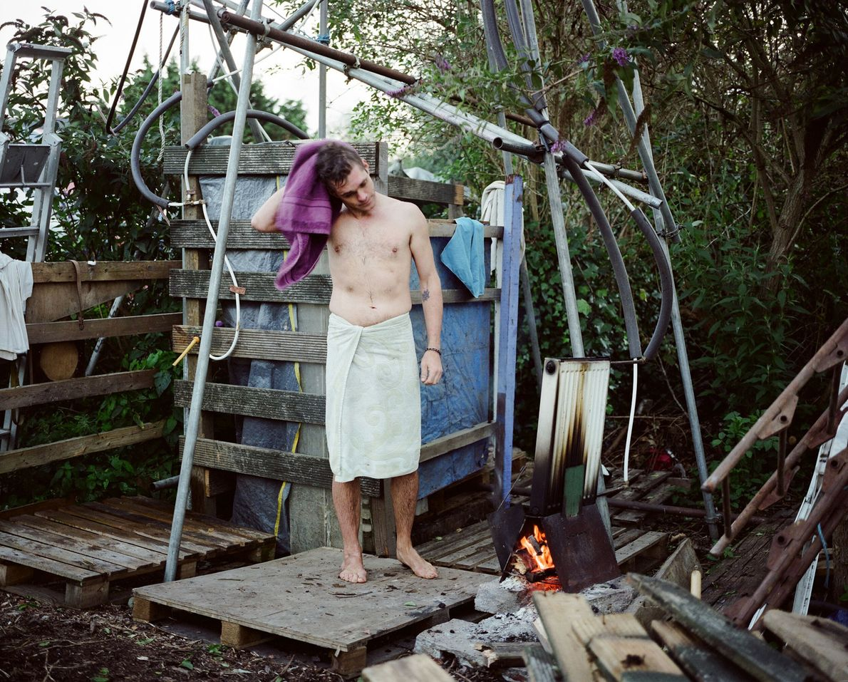 A man dries off after a shower at the Grow Heathrow shower block. The group heats ...