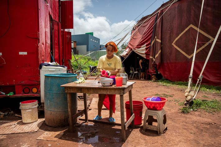 Lilian washes dishes in the improvised kitchen area next to their living quarters. The performers sold ...