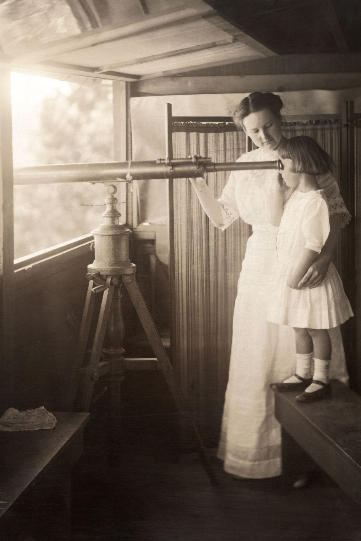 A mother and daughter watch for a signal fire through a telescope in Arizona's Grand Canyon.