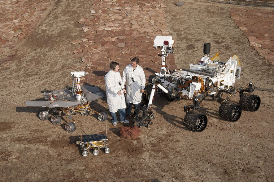Two engineers stand with three generations of Mars rovers developed at JPL. At center is a flight spare of the 1997 Sojourner Mars rover. To the left is a working sibling to Spirit and Opportunity; to the right stands a test version of its successor, Curiosity.