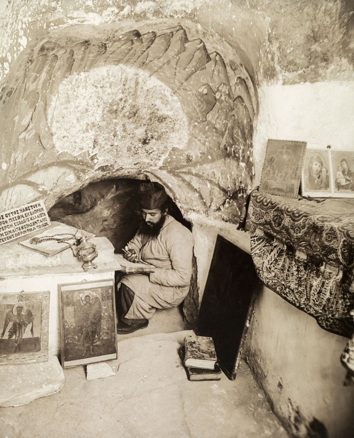 An Orthodox monk reads in a cave in Israel where the prophet Elijah is believed to ...