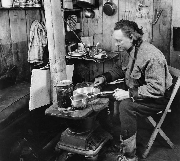 "The ultimate self-isolator, Admiral Richard Byrd prepares a meal at ""Advance Base"", his remote hut on ..."