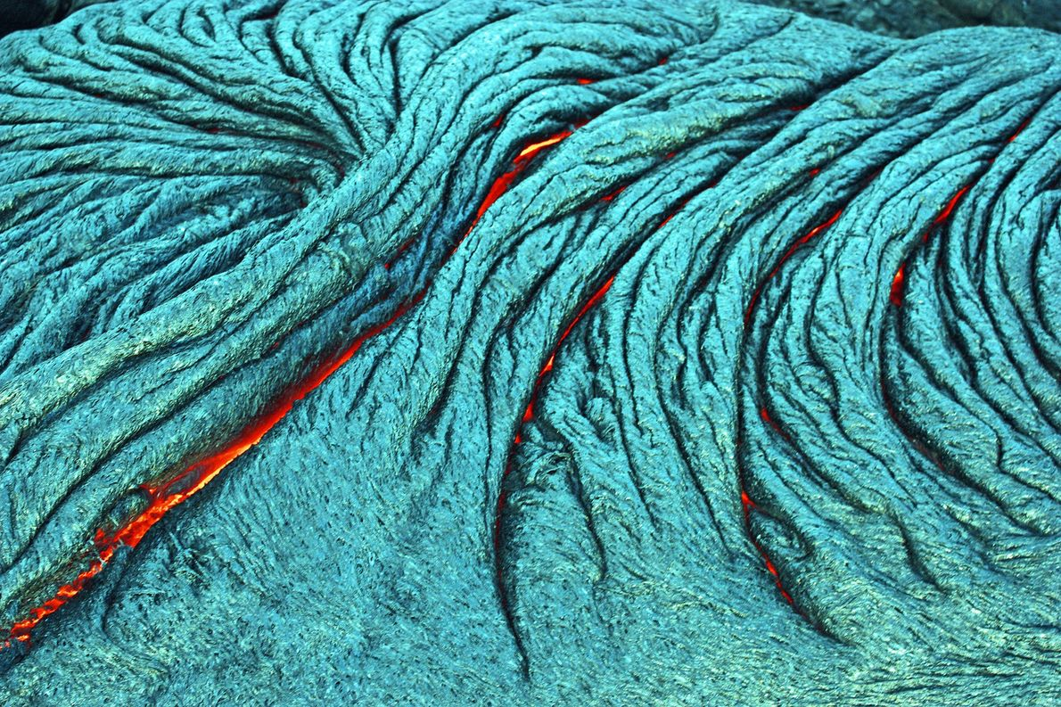 Active pahoehoe lava flows, like the one seen here, are produced by superheated flowing magma.  …