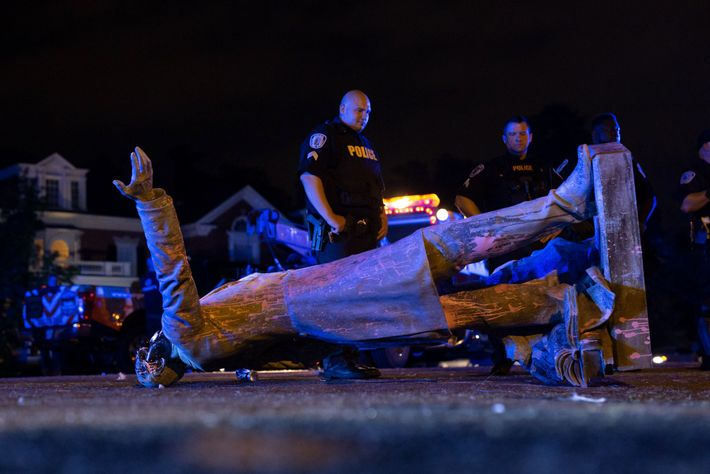 A statue of Jefferson Davis lies on the street after protesters pulled it down in Richmond, ...