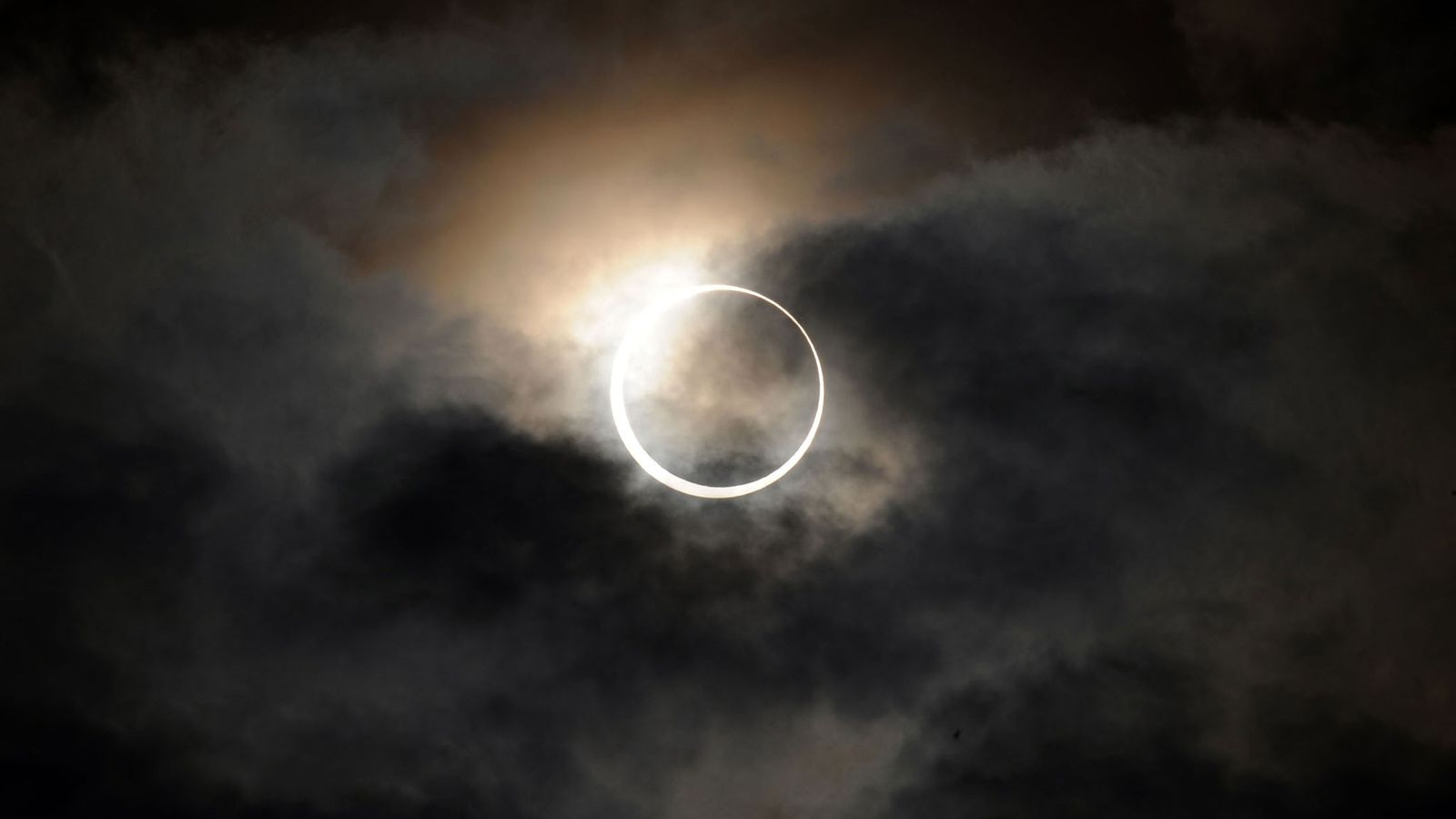 An annular solar eclipse shines through the clouds over Tokyo in May 2012. People across the ...