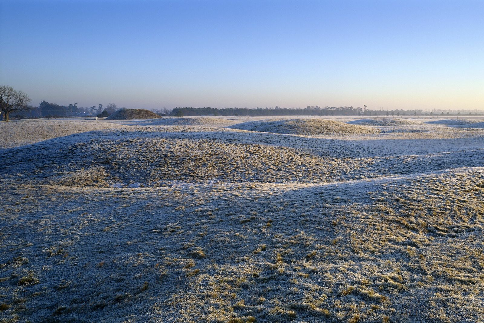 A view across the frost-covered burial mounds at Sutton Hoo on a dawn morning. Part of ...