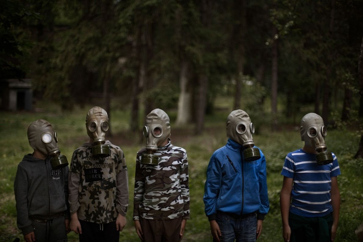 A group of young Ukrainian boys are being taught how to put a gas mask on ...