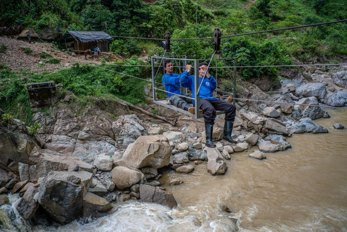 Two biologists from the team cross a river using zip lines that farmers use every day. ...
