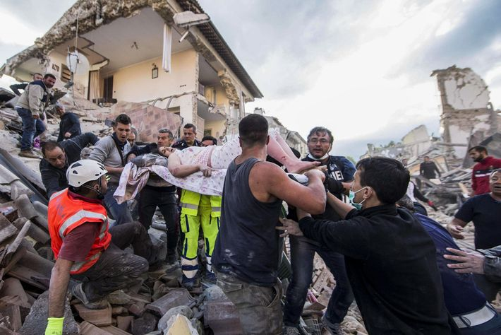 Rescuers carry an injured woman amid the rubble of collapsed buildings in Amatrice, central Italy, following ...