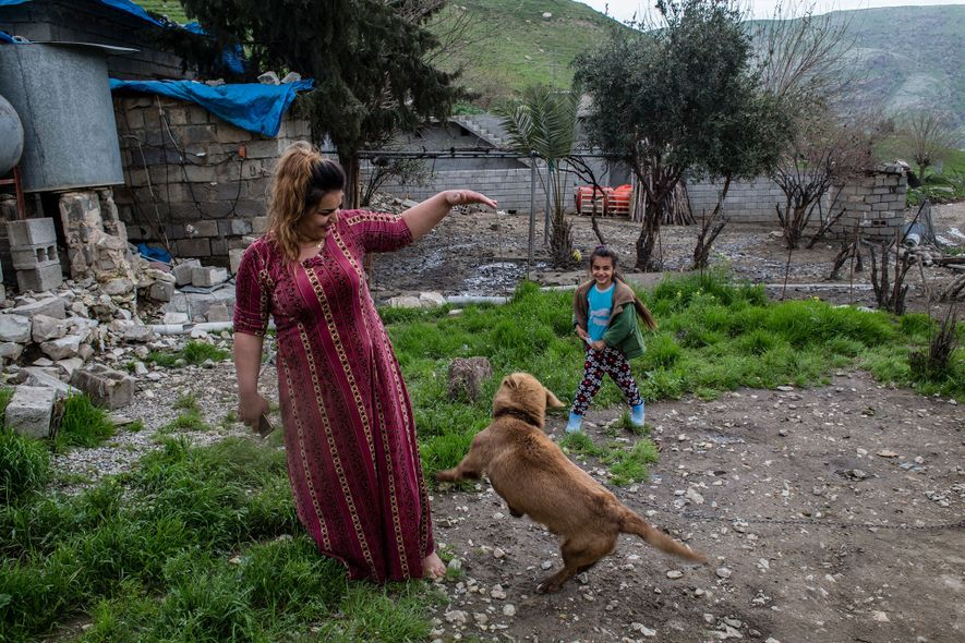A woman in Iraqi Kurdistan plays with the family dog in a village where wildfire recently ...