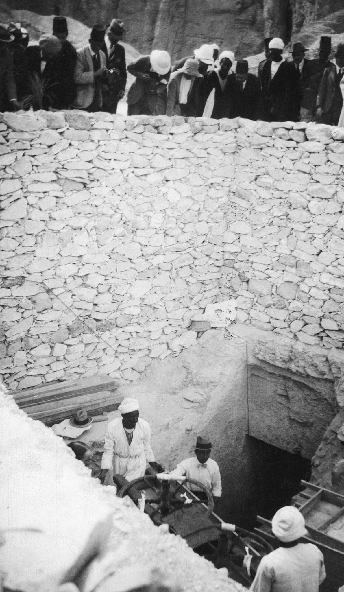 As the curious crowd looks on, a crew of labourers carefully removes parts of one of ...