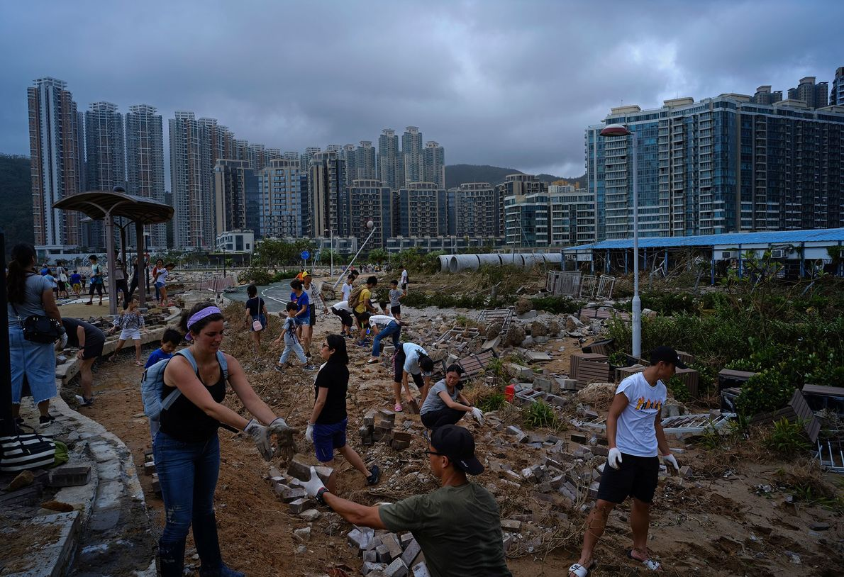 People help to clean debris left behind by Typhoon Mangkhut on the waterfront in Hong Kong. ...