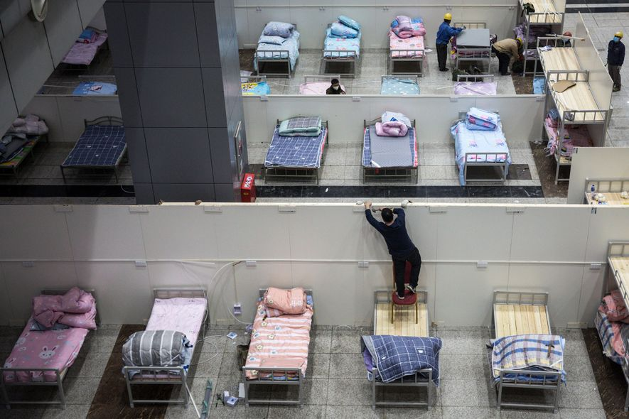 Workers prepare beds at Wuhan International Conference and Exhibition Centre.