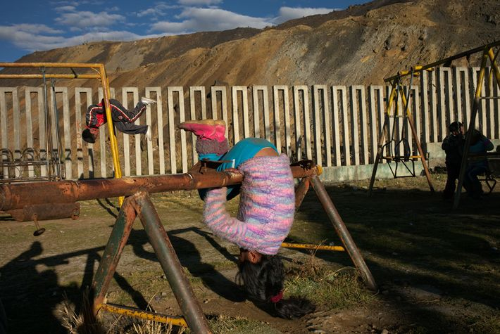 Piles of contaminated mine tailings loom over a playground in the Paragsha neighbourhood. Dust laced with ...