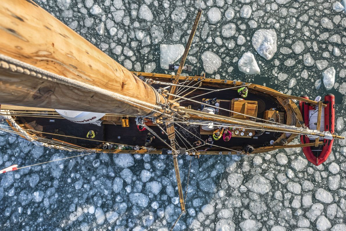 """A crows nest perspective taken from the mast top whilst sailing a traditional schooner through arctic …"