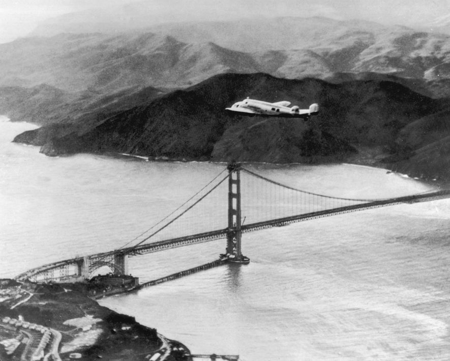 Amelia Earhart and Fred Noonan fly over the Golden Gate Bridge at the start of a planned round-the-world flight in 1937. The trip was abandoned after the plane crashed on take off in Hawaii. A subsequent attempt ended when the aviators went missing in the Pacific.