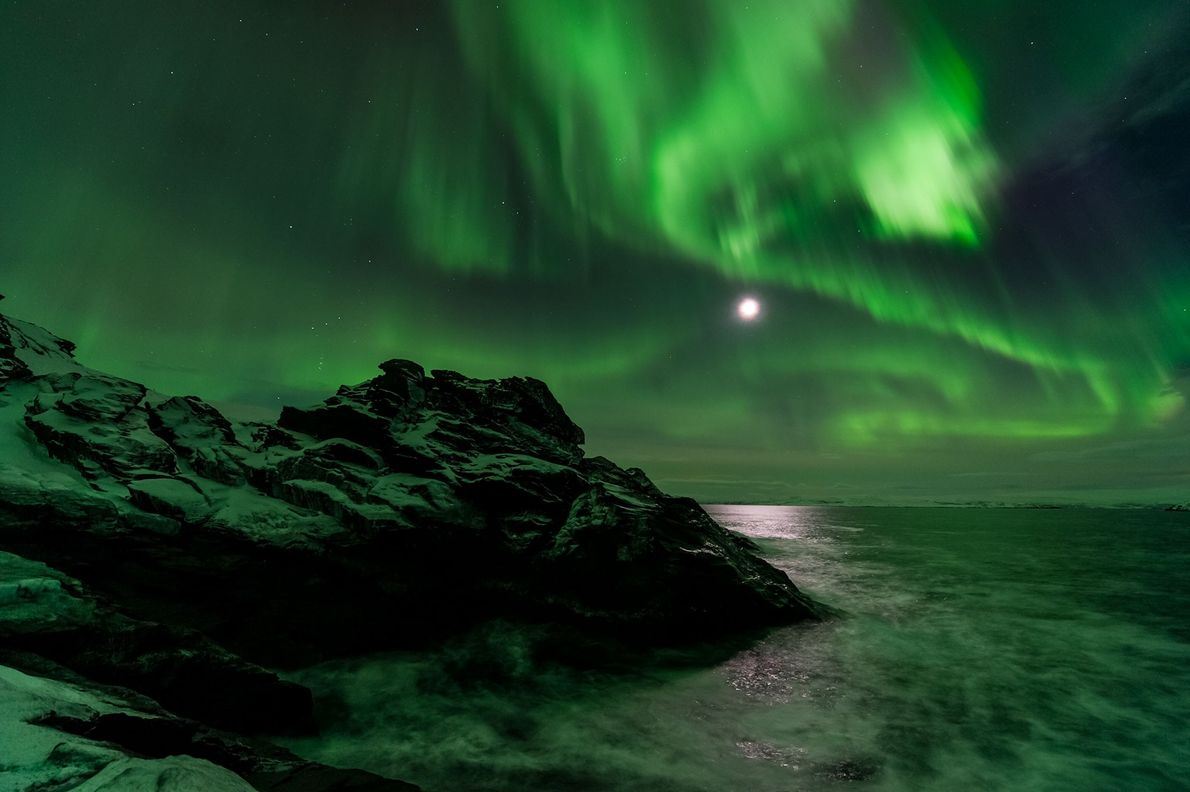 The moon shines through a northern lights display seen from Laksefjorden in Norway.