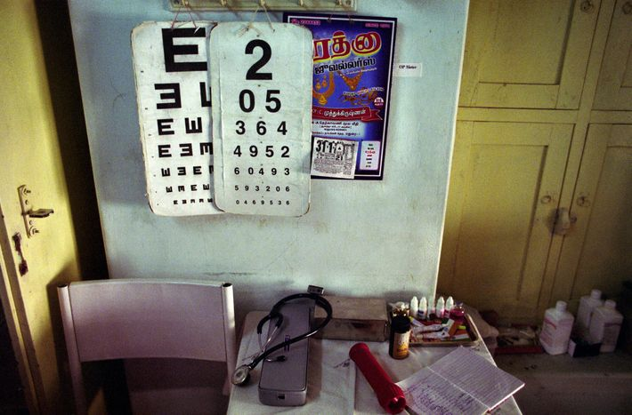 An eye testing chart and basic equipment sit in a small outreach hospital in rural India. ...